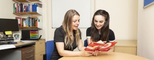 A female student and female Academic Tutor talking and looking at a leaflet together